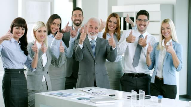 группа деловых людей, держа их пальцы вверх - thumbs up стоковые видео и кадры b-roll