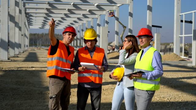 Group of Business People in Yellow and Red Hardhats Discuss a Project on Site Under Construction