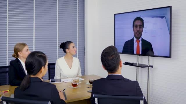 gruppe von geschäftsleuten, blick auf eine leinwand mit video-konferenz-meeting im büro - konferenzraum videos stock-videos und b-roll-filmmaterial