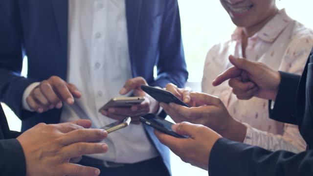 stockvideo's en b-roll-footage met groep van mensen uit het bedrijfsleven met mobiele telefoons - vier personen