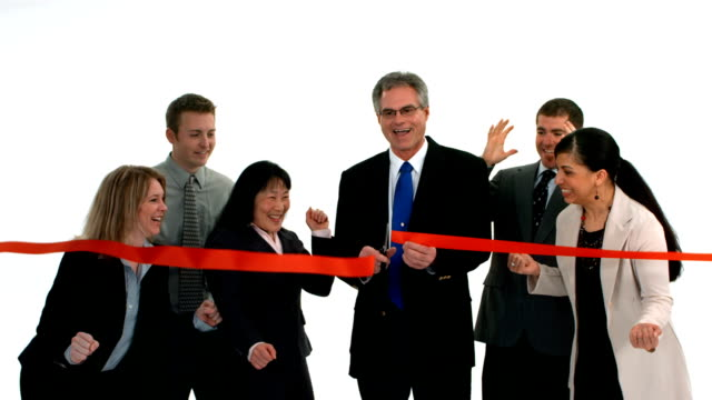 Group of businesspeople cut ribbon and celebrate, slow motion video