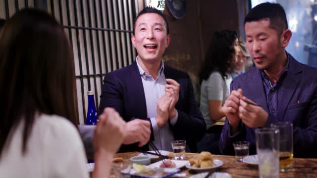 stockvideo's en b-roll-footage met groep ondernemers ontspannen in een japanse izakaya - ongezond leven
