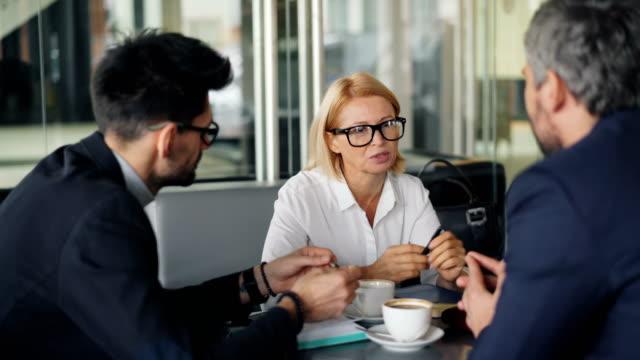 grupp av affärs män som talar i coffee shop diskuterar partnerskap - gemensam samlingsplats bildbanksvideor och videomaterial från bakom kulisserna