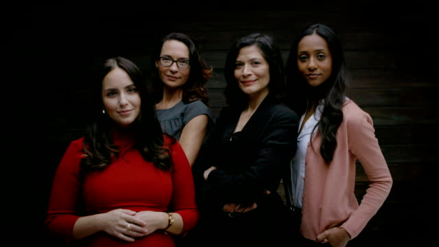 Group of businesswomen standing together Group of businesswomen standing together against wooden wall in office group of people stock videos & royalty-free footage