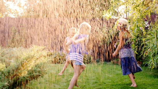 Group of carefree cheerful children playing in the garden. Running around barefoot on the grass under the jets of water or rain