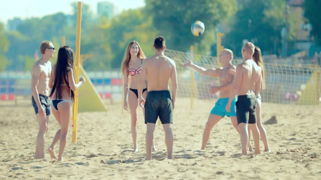 Group of carefree guys and teenage girls enjoying beach volleyball on the sand Group of carefree guys and teenage girls enjoying beach volleyball on the sand beach volleyball stock videos & royalty-free footage