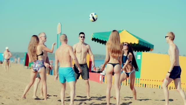 Grupo de despreocupados chicos y chicas adolescentes disfrutar de voleibol de playa en la arena - vídeo