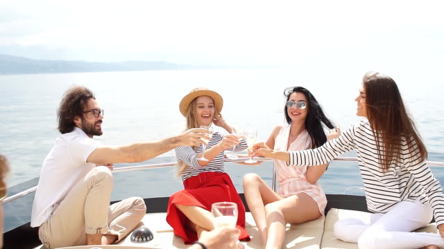 Group of Caucasian high school students participating in sea excursion to picturesque islands. Business or educational travelling on yacht. Cruise vacation