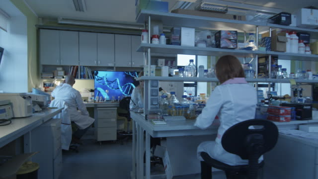 Group of caucasian scientists in white coats are working in a modern laboratory. – Video