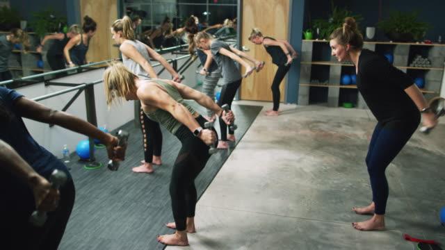 en grupp av kaukasiska kvinnor i blandade åldrar utföra triceps övningar med hantlar i en barre studio - balettstång bildbanksvideor och videomaterial från bakom kulisserna