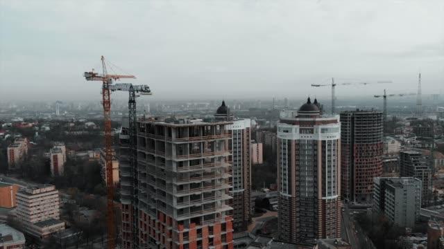 grupp kaukasiska arbetare i orange hjälmar arbetar på taket av oavslutad byggnad. arbetstagare vid byggande av höghus bostadskomplex - stenhus bildbanksvideor och videomaterial från bakom kulisserna