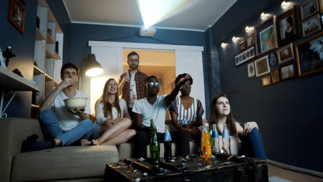 Group of cheerful multiethnic friends watch sports on TV at home using projector with snacks and drinks slow motion. Group of cheerful multiethnic friends watch sports on TV at home using projector with snacks and drinks slow motion. Diverse happy young company of students enjoy online video web streaming cinema. international match stock videos & royalty-free footage