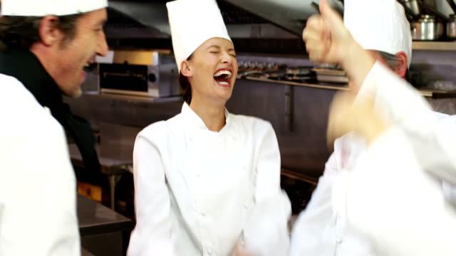 vídeos de stock e filmes b-roll de grupo de cozinheiros a celebrar e colocando suas mãos juntas - cooker happy