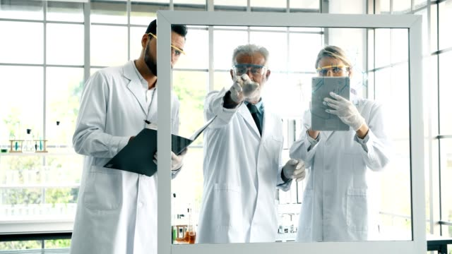 group of chemist working in a lab, taking notes and writing on glass display. - debate стоковые видео и кадры b-roll