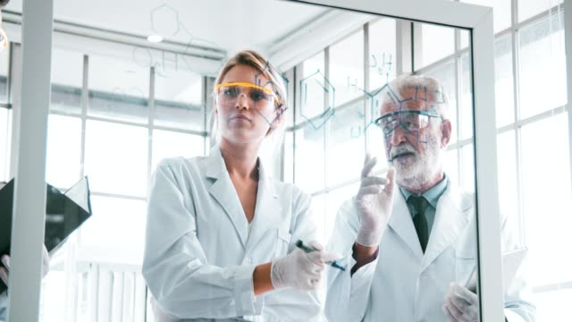 4k: gruppe von chemikern studium formel auf transparente board - wasserstoff stock-videos und b-roll-filmmaterial