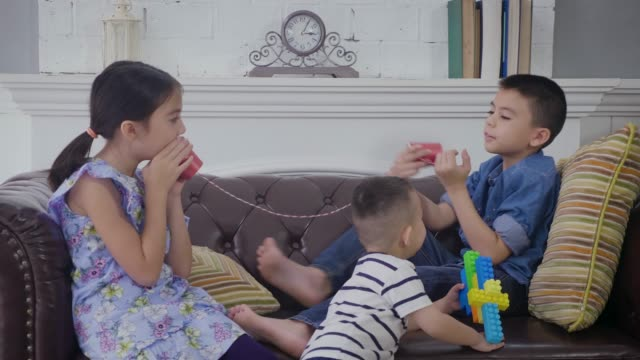 Group of children enjoying playing tin can phone together in the living room at home