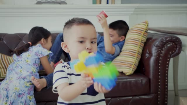 Group of children enjoying playing together in the living room at home
