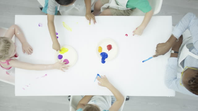 group of children finger-painting on a clean white table - kids drawing стоковые видео и кадры b-roll