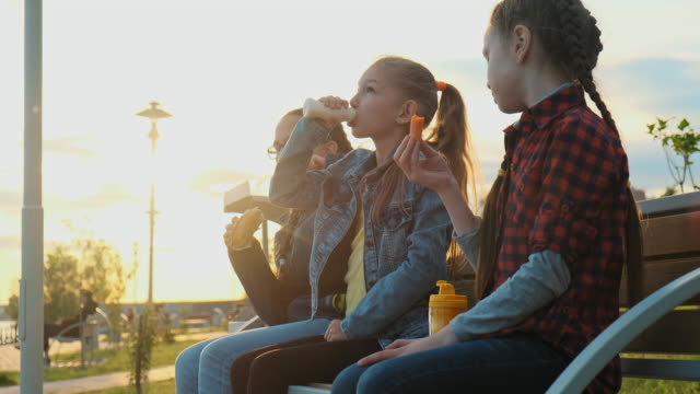 a group of children friends are sitting on a bench and eating. - bench stock videos & royalty-free footage