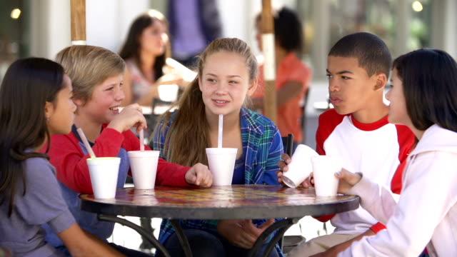 gruppo di bambini di rilassarsi insieme in café - preadolescente video stock e b–roll