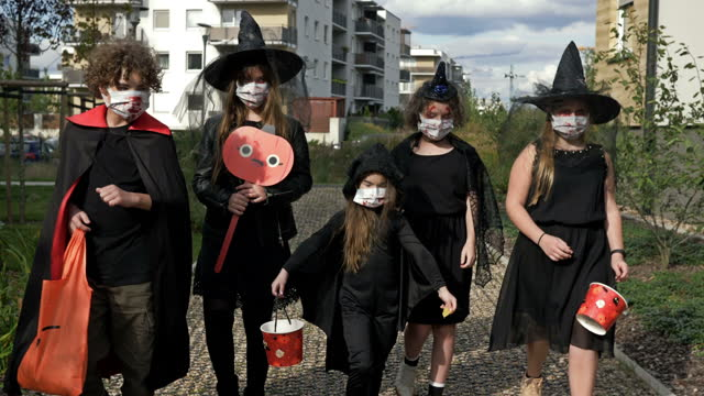 Group of children in black masquerade costumes are walking down the street. Everyone has medical masks on their faces. Halloween during the covid19 coronavirus pandemic Group of children in black masquerade costumes are walking down the street. Everyone has medical masks on their faces. Halloween during the covid19 coronavirus pandemic. 4K. halloween covid stock videos & royalty-free footage