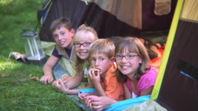 group of children in tent smiling at camera - ligga på mage bildbanksvideor och videomaterial från bakom kulisserna
