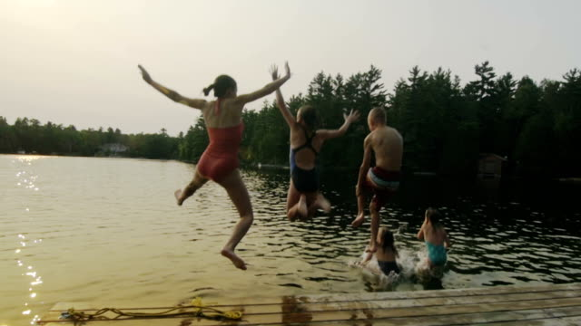 Group of children jumping off dock Five kids, brothers and sisters, jumping off the dock at the cottage at sunset for fun. swimming stock videos & royalty-free footage