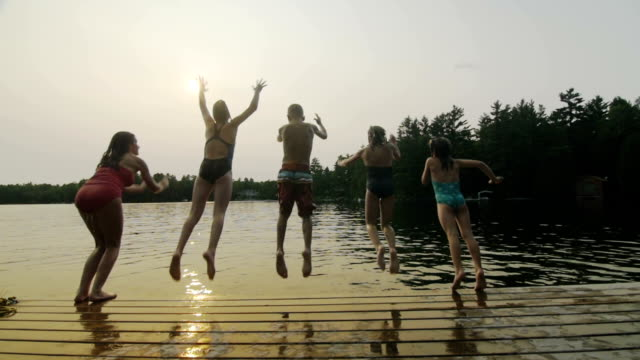 group of children jumping off dock - lakes stock videos and b-roll footage