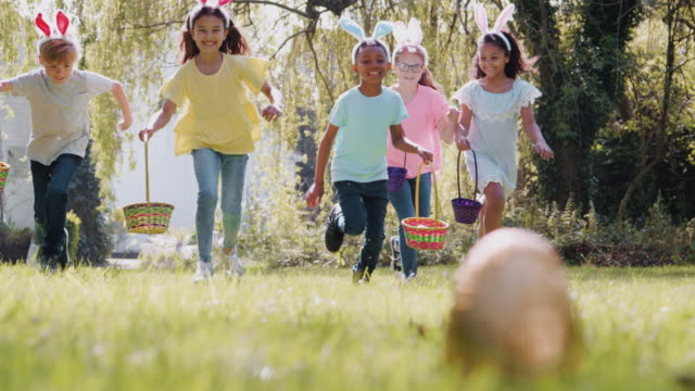 Group of children on Easter egg hunt running across garden and picking up chocolate egg to put into basket - shot in slow motion