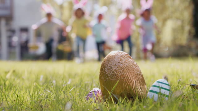 Group of children on Easter egg hunt running across garden towards chocolate egg - shot in slow motion