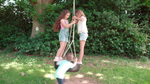 Group Of Children Playing On Tire Swing In Garden video