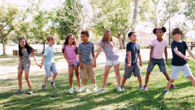 Group Of Children With Friends In Park Dancing And Flossing