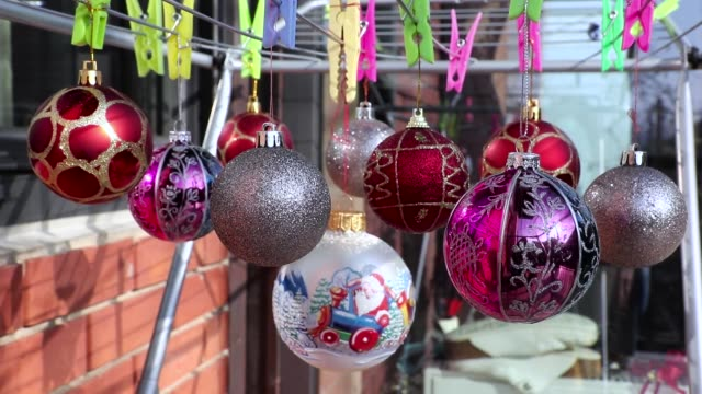 Group of Christmas Balls Ornaments hanging on the clothespin on the  Clothes Drying Rack.