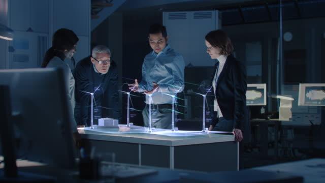 vídeos de stock, filmes e b-roll de grupo de engenheiros civis trabalhar com holográfico realidade aumentada 3d turbina eólica modelo. tecnologicamente avançado office professional people use virtual reality modeling software application. - holograma