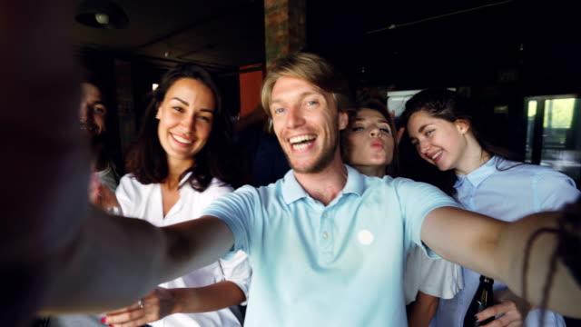 Groupe de collègues sont confondus selfie, jeune homme tient la caméra et posant, ses collègues sont maintenant des boissons en bouteilles, riant et regardant la caméra. - Vidéo