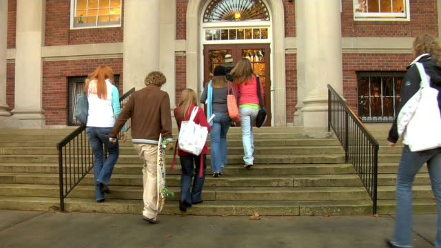 group of college students walk into building - school building bildbanksvideor och videomaterial från bakom kulisserna