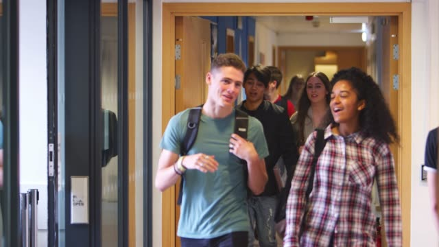 group of college students walking through college corridor - teenagers stock videos and b-roll footage