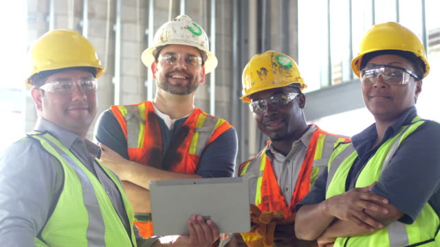 group of construction workers looking at digital tablet - operatore edile video stock e b–roll