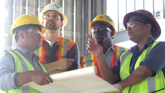 group of construction workers looking at plans - operatore edile video stock e b–roll