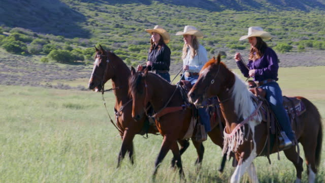 Group of Cowgirls Horse Riding Across a Paddock