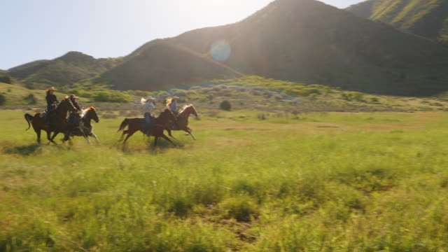 Group of Cowgirls Horse Riding Fast Through a Paddock