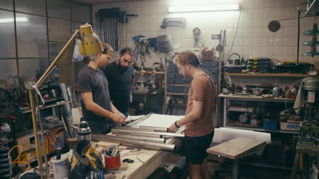 Group of craftsmen designing new product in workshop