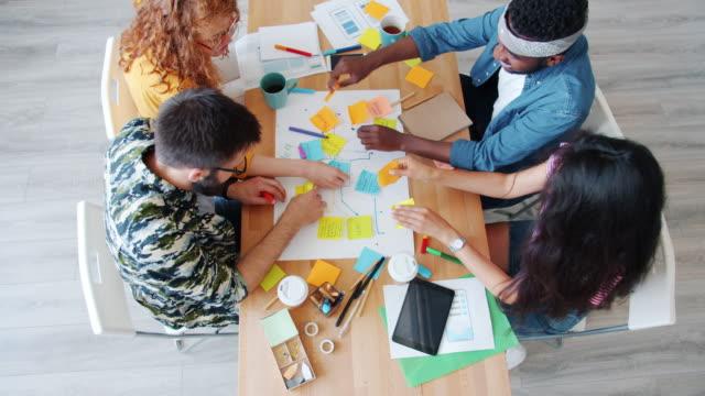 プロジェクトの結合で働くテーブルに急いでテーブルに急いでクリエイティブな人々のグループ - 支えられた点の映像素材/bロール