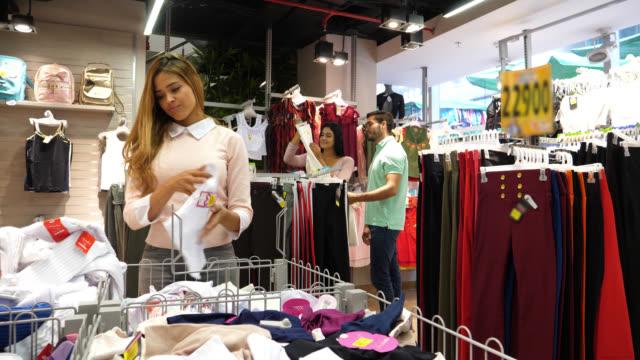 stockvideo's en b-roll-footage met groep klanten bij een zuinigheid winkel kiezen van kleding - discountwinkel