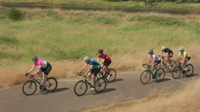group of cyclists on scenic country road. - triatleta video stock e b–roll