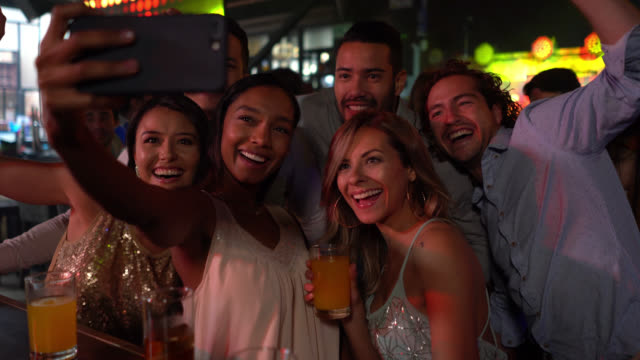 Group of diverse friends having fun at a bar drinking cocktails and taking a selfie video