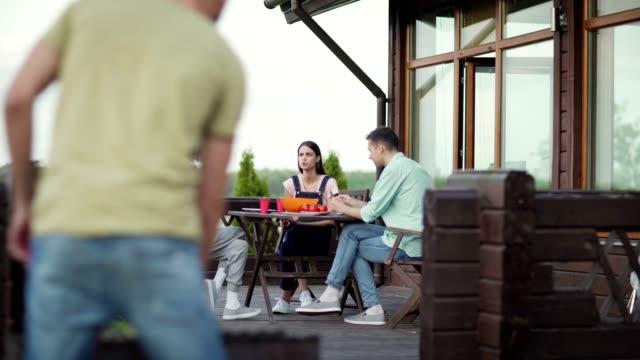 vidéos et rushes de groupe d'amis divers parlant s'asseyant à la table sur la terrasse en bois de maison de campagne à la partie de bbq. jeune homme préparant des légumes grillés et rejoignant des amis - man drinking terrace