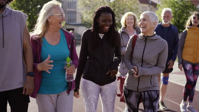 group of diverse people walking together and talking after their dance class - baby boomers stock videos & royalty-free footage