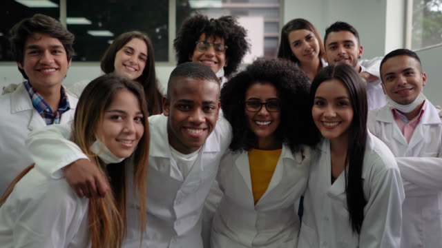 Group of diverse students during science class wearing lab coats, protective gloves and masks smiling at camera