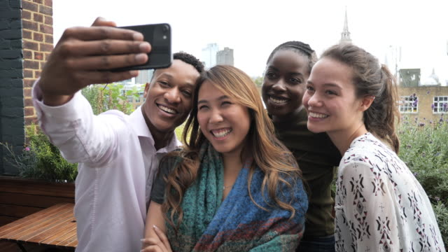 group of diverse young people taking selfie and laughing - età miste video stock e b–roll